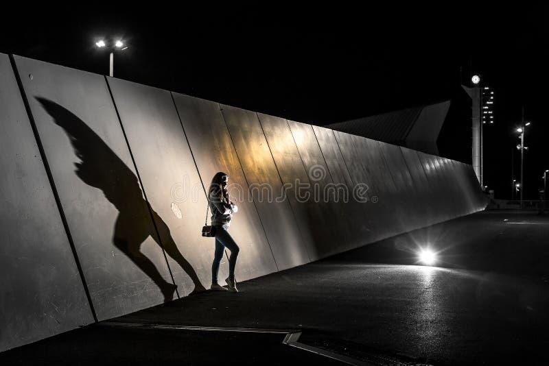 站立在墙壁旁边的少妇剪影概念性照片在晚上 库存照片