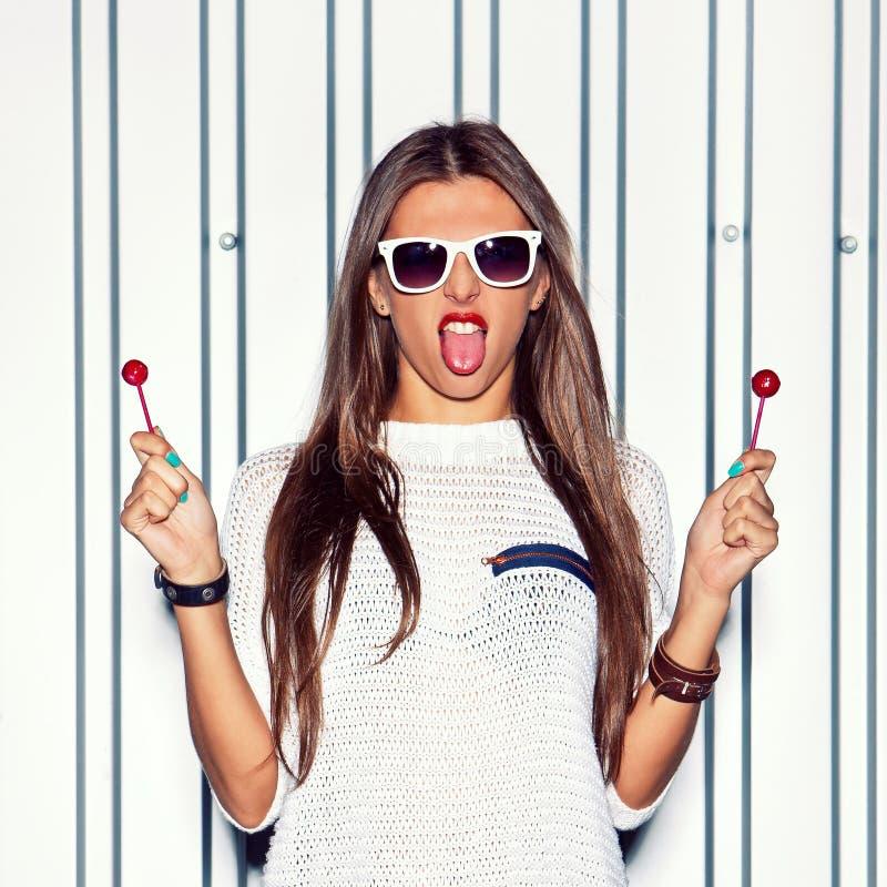 站立在墙壁附近的一个美丽的女孩举行两红色 免版税图库摄影