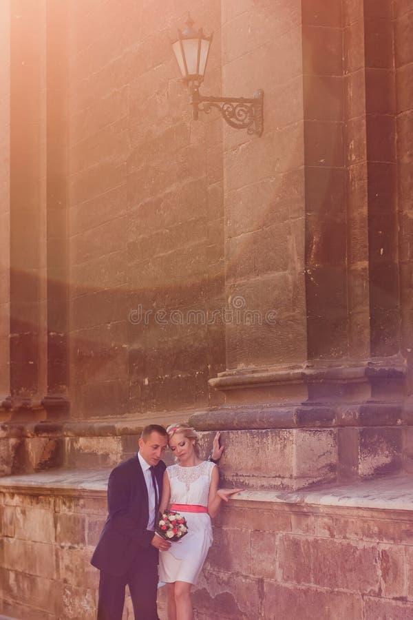 站立在墙壁附近的婚礼夫妇 免版税库存图片