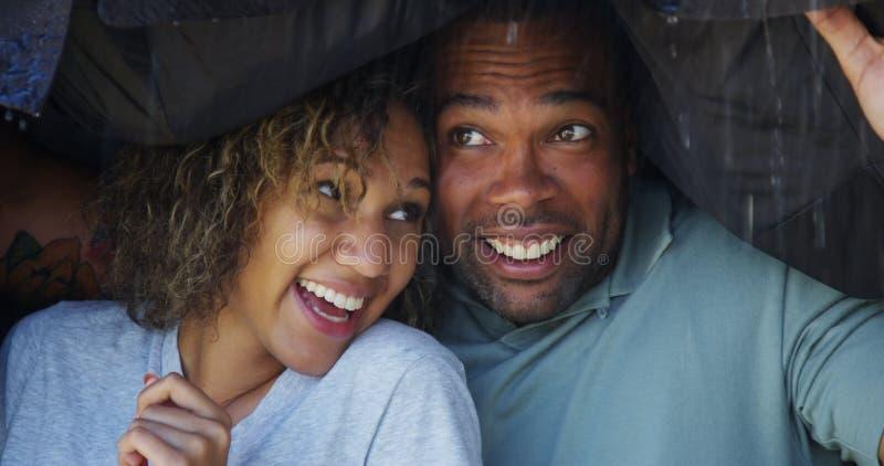 站立在外套下的黑夫妇设法没得到湿 免版税图库摄影