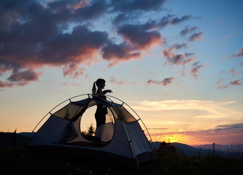 站立在外形的一个可爱的女孩的剪影在帐篷附近在早晨天空下在破晓 免版税库存照片