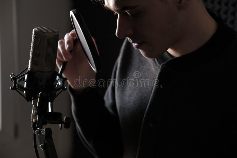 站立在外形的一张年轻人` s面孔的特写镜头在话筒附近 图库摄影