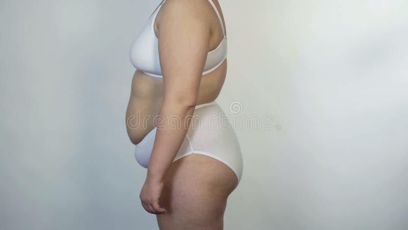 站立在外形的白色内衣的肥头大耳的女性,超重人 免版税库存照片