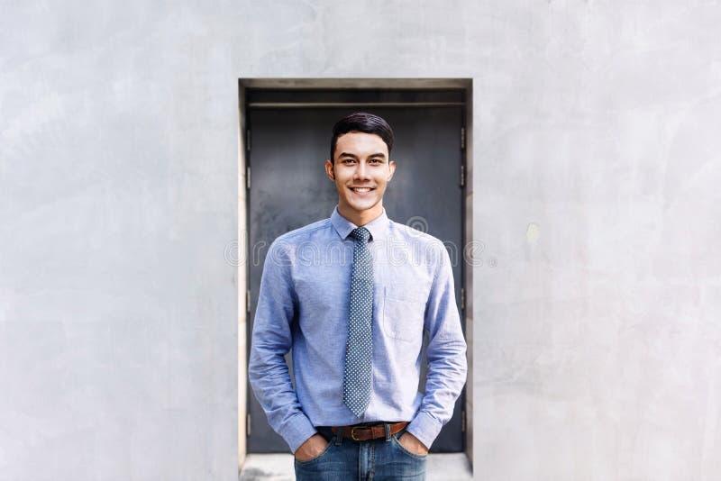 站立在外部大厦的愉快的年轻商人画象  免版税库存照片