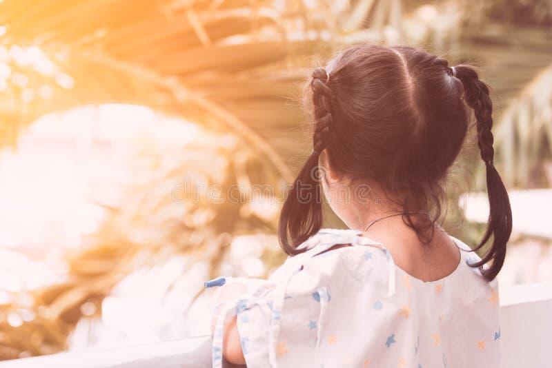 站立在外部屋子的后面观点的病的儿童女孩休息里 库存照片