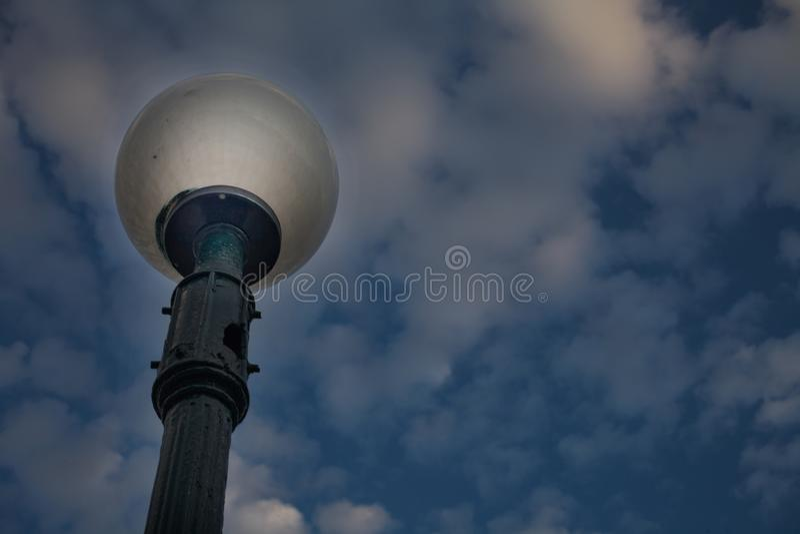站立在多云昏暗的天空下的室外灯岗位角度图  一个街道灯笼特写镜头射击有抽烟的圆的 免版税图库摄影