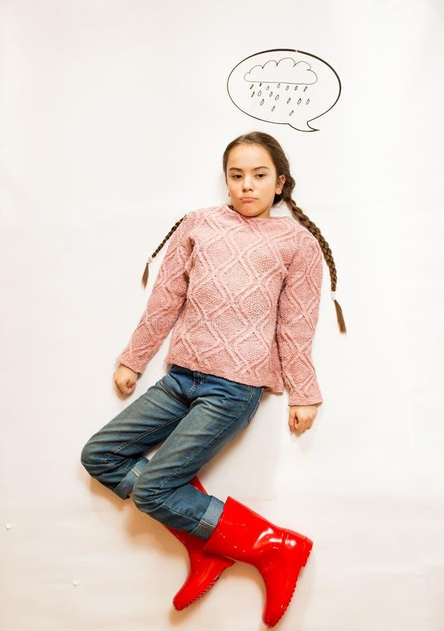 站立在多雨云彩下的胶靴的哀伤的女孩 免版税库存图片