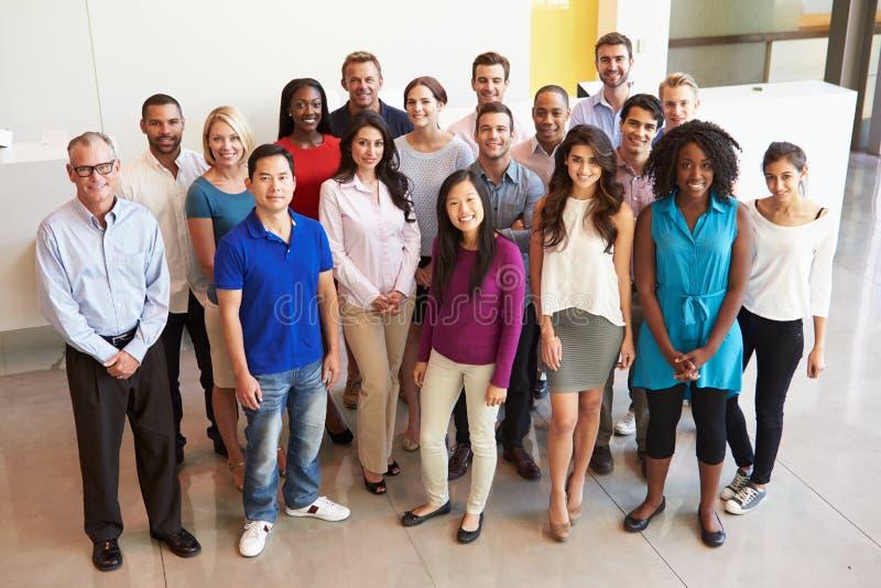 站立在大厅的多文化办公室工作人员画象  库存图片