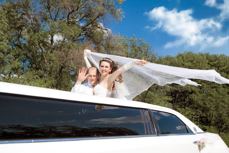 站立在大型高级轿车挥动的新娘和新郎 库存图片