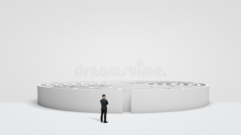 站立在大白色圆的迷宫前面的一个微小的商人在入口旁边 免版税库存图片