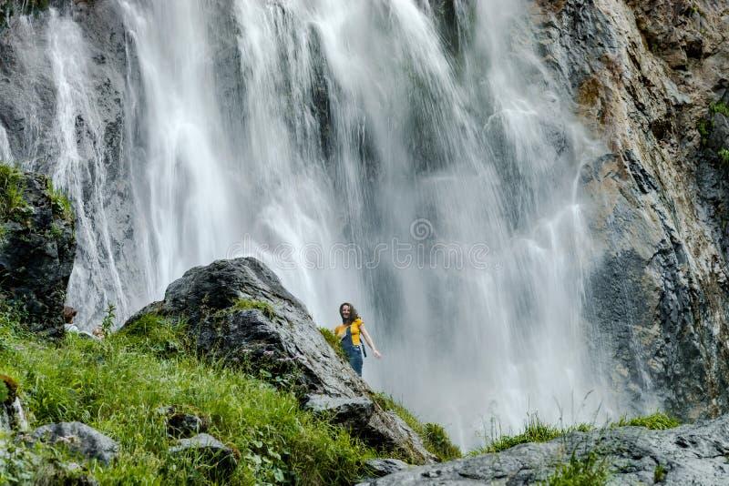 站立在大石近的瀑布的年轻十几岁的女孩 库存图片