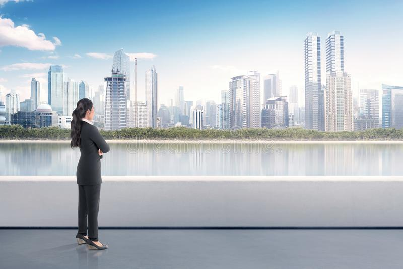 站立在大阳台和看的亚裔女商人画象  免版税库存照片