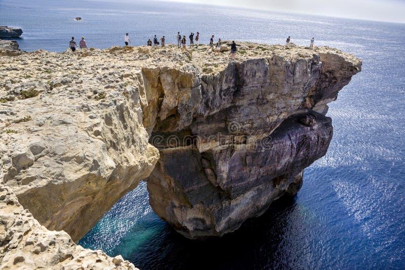 站立在天蓝色的窗口里的人们在马耳他 库存照片