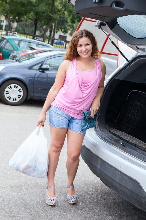 站立在她的与塑料购物袋的suv附近的愉快的夫人 库存图片