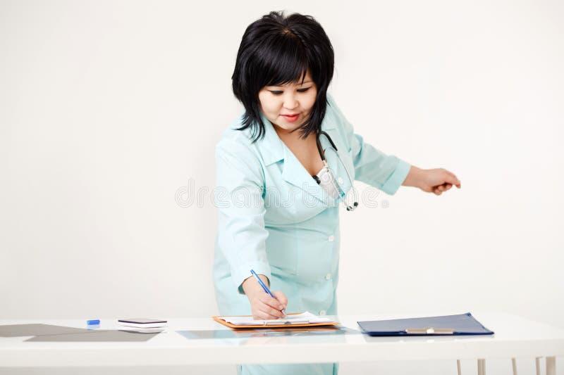 站立在她的书桌的逗人喜爱的弯曲的女性医生在纸写勘测的结果由笔,医学实验室外套与 库存照片