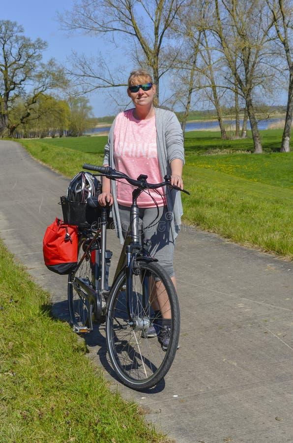 站立在她的在农村围拢的自行车附近的妇女在Lueneburg荒地的易北河 库存图片