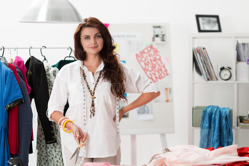站立在她的工作室的女性礼服制造商画象  库存照片