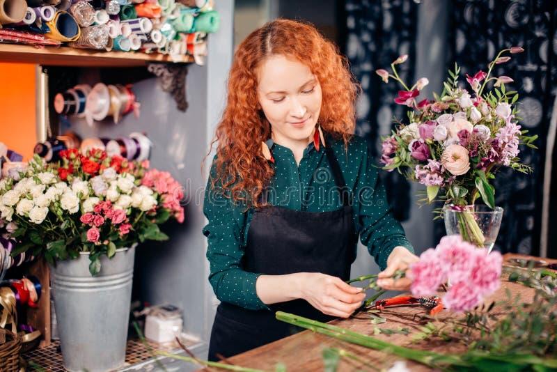 站立在她的工具旁边的美丽的愉快的卖花人在花车间 库存照片