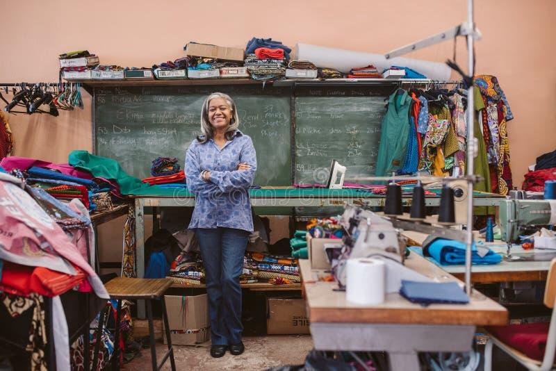 站立在她繁忙的缝合的车间的微笑的成熟裁缝 免版税图库摄影