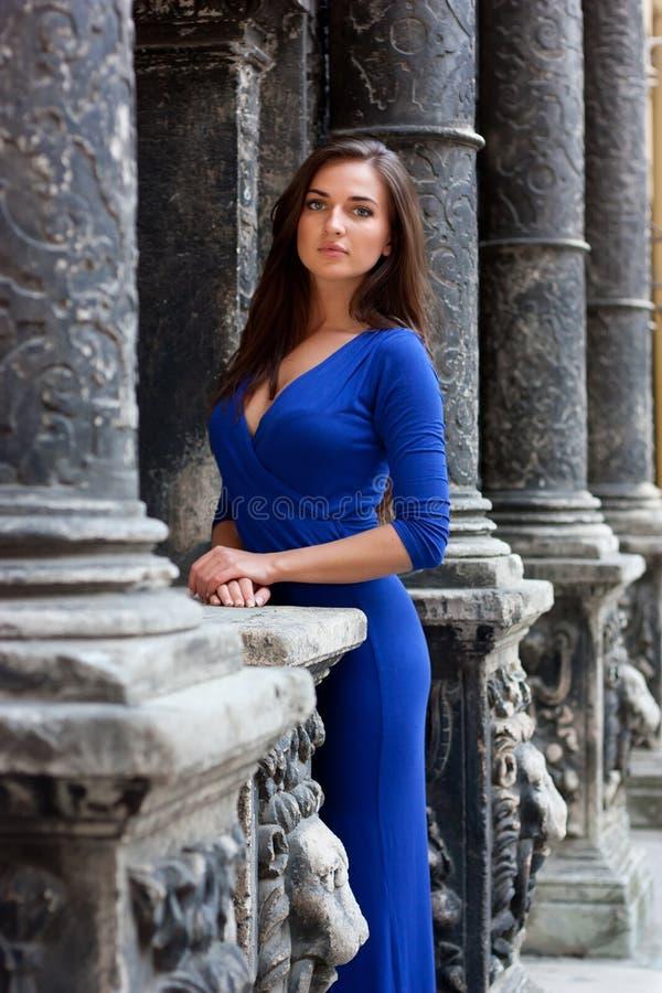 站立在好老墙壁旁边的一件蓝色礼服的时髦的女孩 免版税库存照片