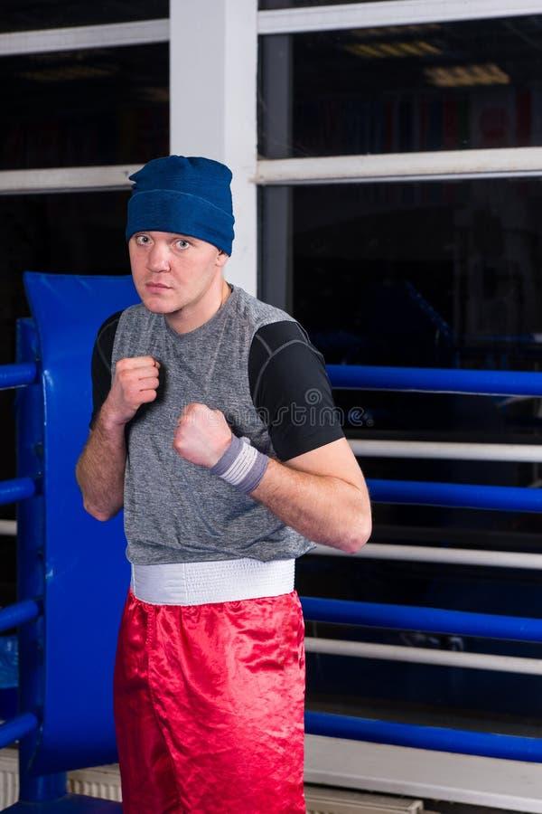 站立在姿势的运动拳击手握紧他的在regul的拳头 库存图片
