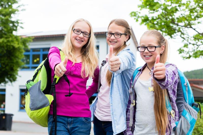 站立在学校前面的小组女孩 库存图片