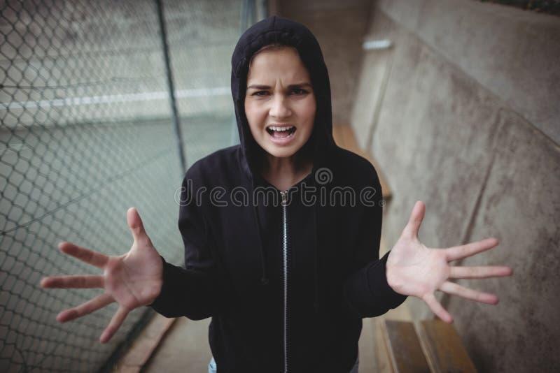 站立在学校校园的恼怒的十几岁的女孩 免版税库存图片