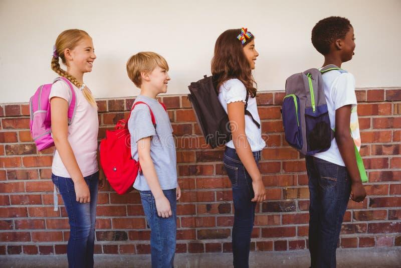 站立在学校走廊的学校孩子 免版税图库摄影