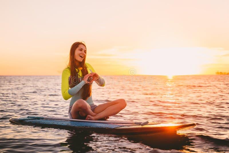 站立在安静的海的桨搭乘有温暖的夏天日落颜色的 愉快的微笑的女孩在船上日落的 库存图片
