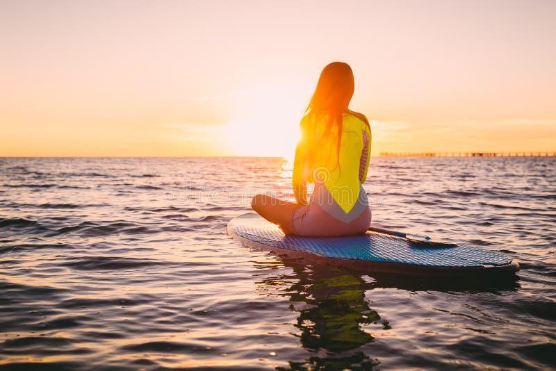 站立在安静的海的桨搭乘有温暖的夏天日落颜色的 放松在海洋 库存照片