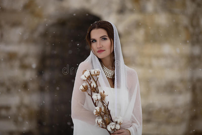 站立在寒冷和拿着棉花花的围巾的年轻新娘 免版税库存照片