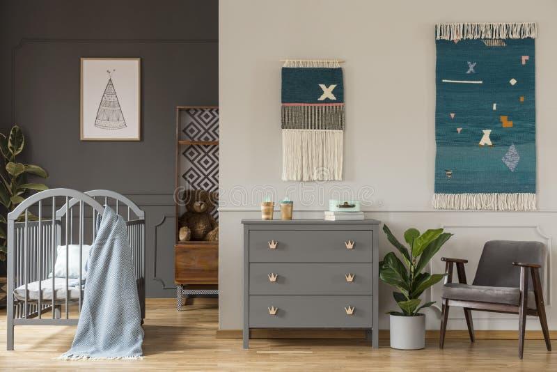 站立在小儿床之间的灰色碗柜的真正的照片和ar 库存照片