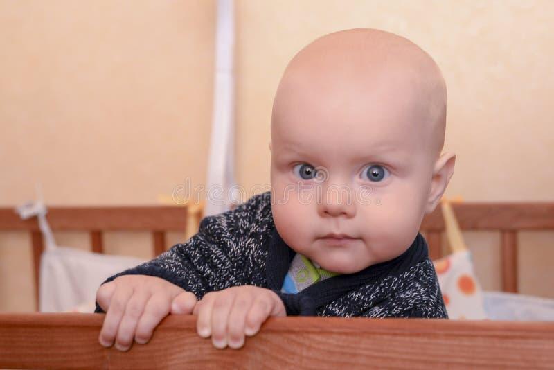 站立在小儿床的滑稽的男婴 图库摄影