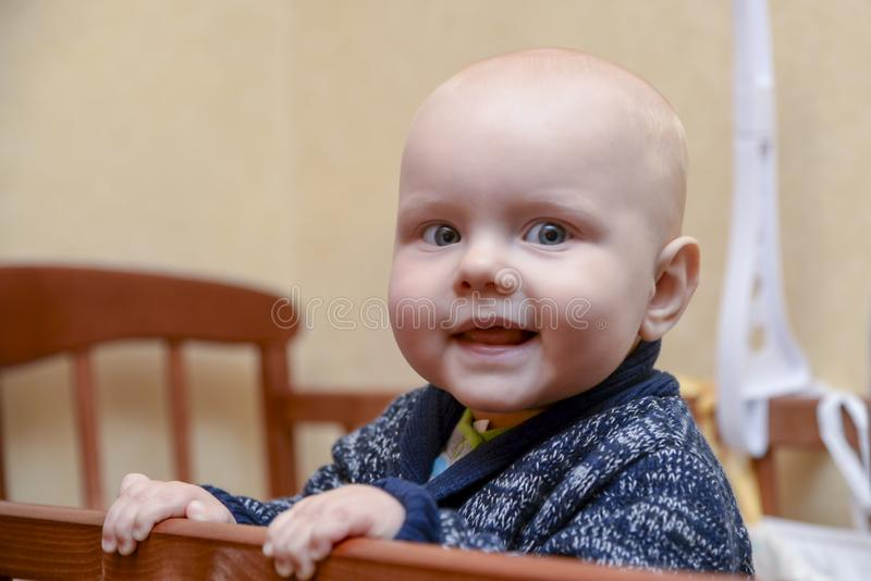 站立在小儿床的滑稽的男婴 库存照片