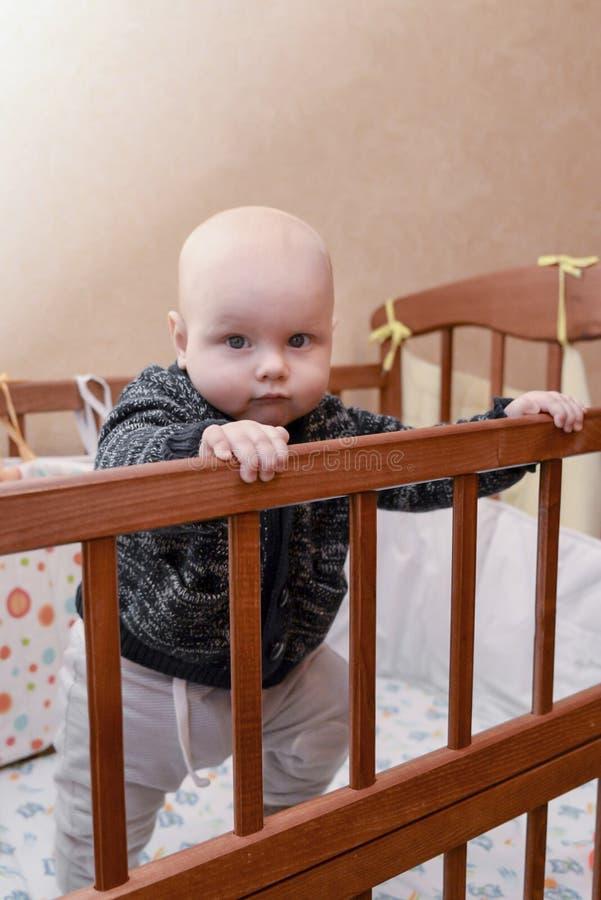 站立在小儿床的滑稽的男婴 库存图片