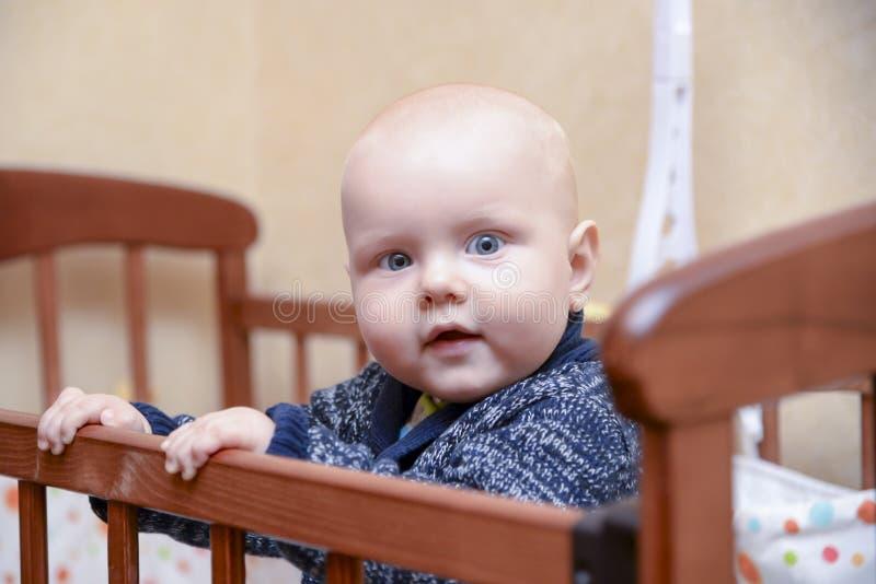 站立在小儿床的滑稽的男婴 免版税库存图片