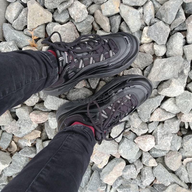 站立在小卵石的运动鞋在 免版税库存图片