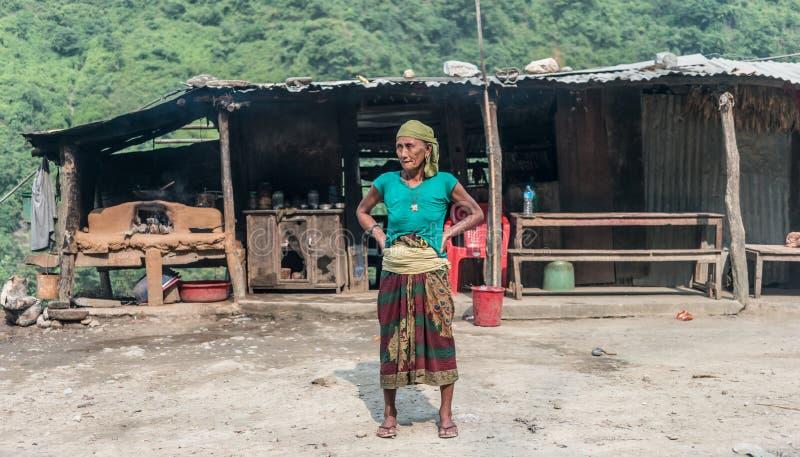 站立在小屋前面的尼泊尔妇女 库存图片