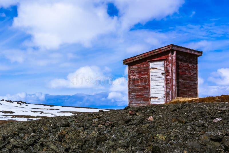 站立在小山的红色木棚子 免版税库存图片