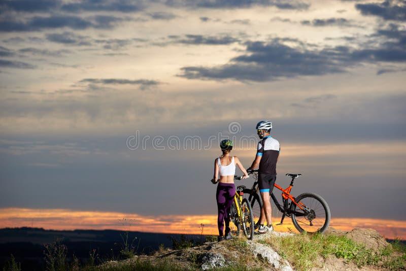 站立在小山的近的自行车和观察风景的骑自行车者夫妇  库存图片