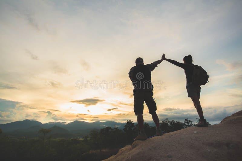 站立在小山顶部和享受在谷、家庭、夫妇、男性和女性的徒步旅行者剪影日出,站立  免版税库存照片