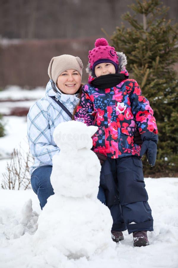 站立在小雪人,冬天季节附近的愉快的母亲和俏丽的女儿画象  库存图片