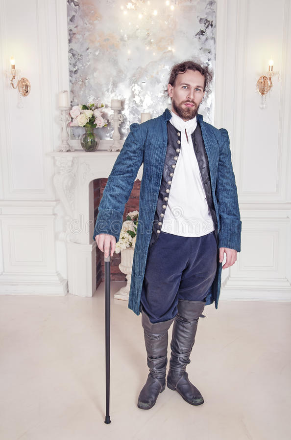 站立在屋子里的中世纪衣裳的英俊的人 库存照片