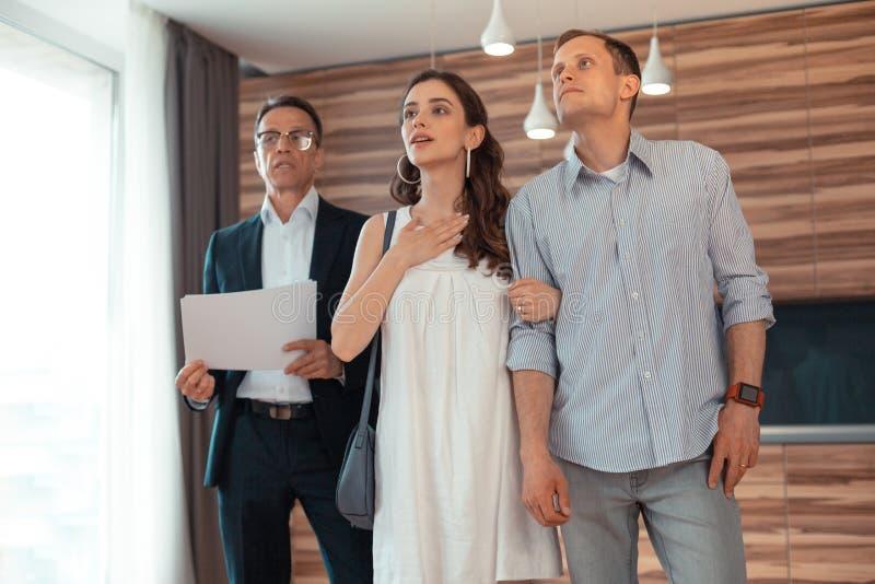 站立在屋子里的夫妇考虑买的房子 图库摄影