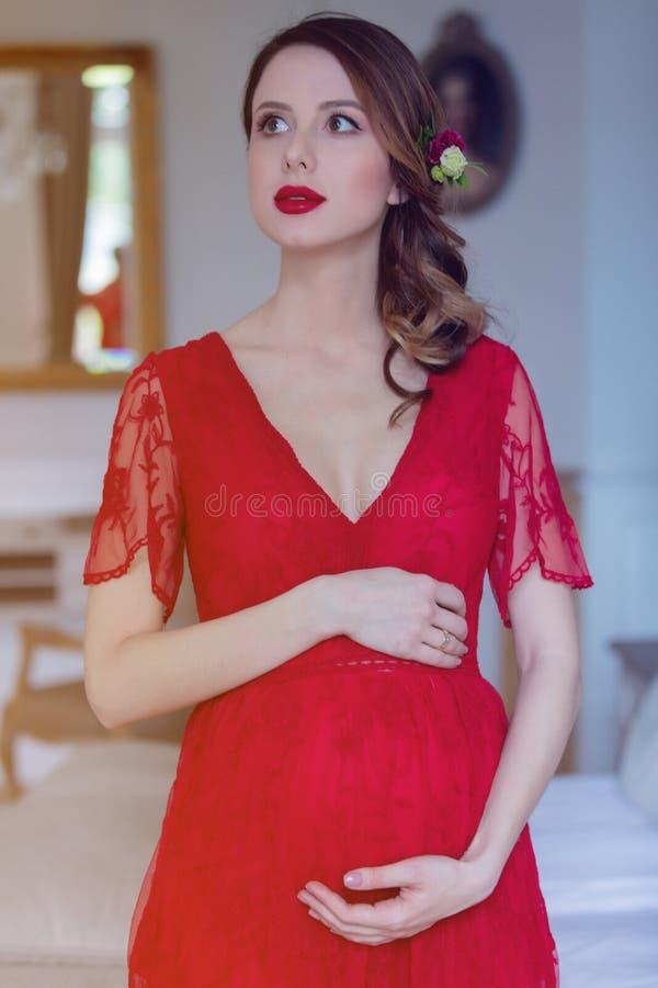 站立在屋子里的红色礼服的少妇 免版税库存照片