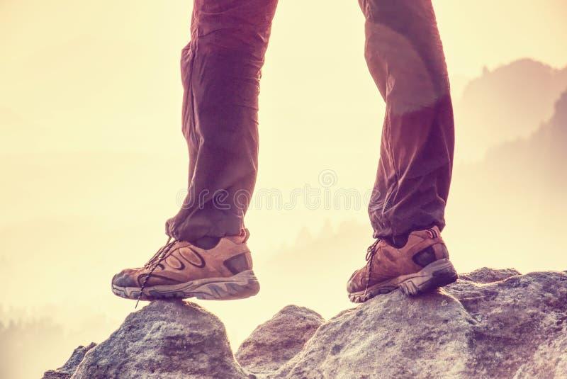 站立在山上面的成功的体育人徒步旅行者腿 室外长裤和迁徙的皮靴 在有薄雾的谷的足迹 免版税库存照片
