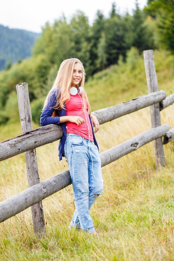 站立在山坡的年轻时髦的女孩近的篱芭 免版税库存照片