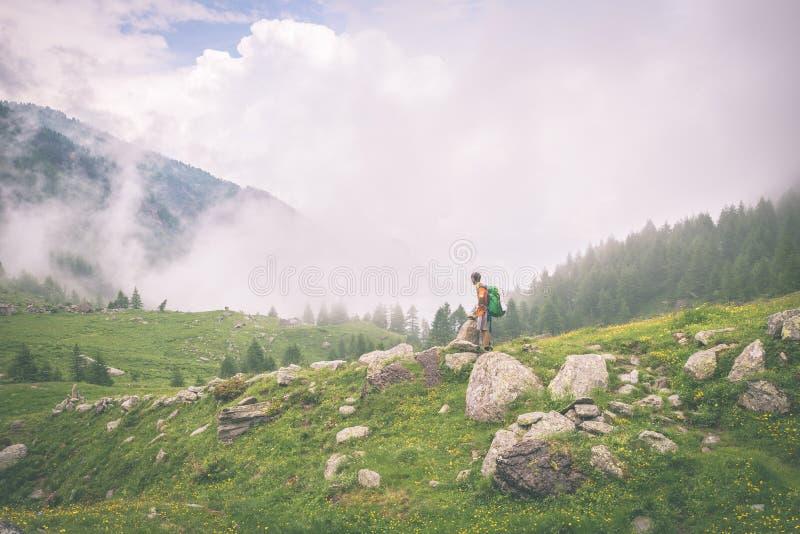 站立在山小径的背包徒步旅行者,被定调子 免版税库存照片