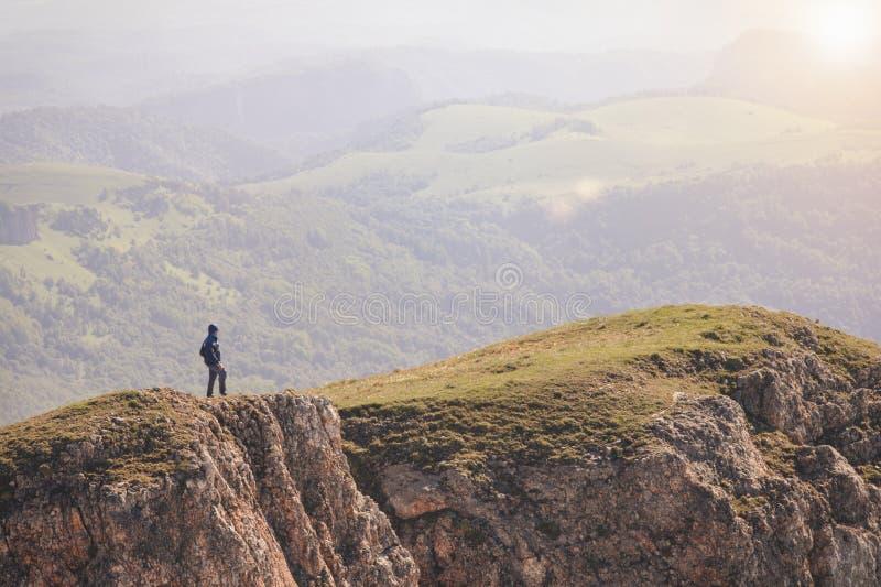 站立在山峭壁的人旅客室外 免版税图库摄影