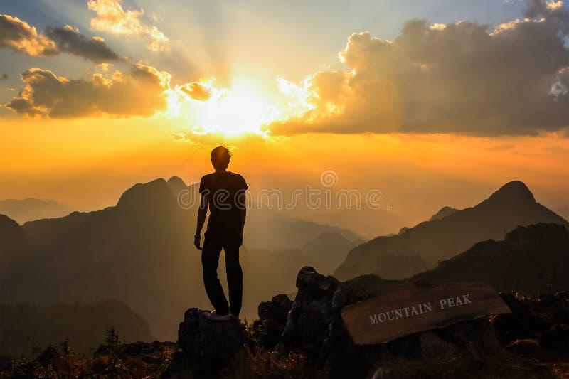 站立在山峰的人在日落 免版税库存图片